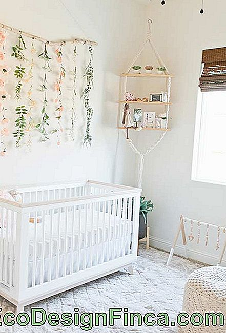 Clothesline with artificial flowers in the decoration of the small baby room