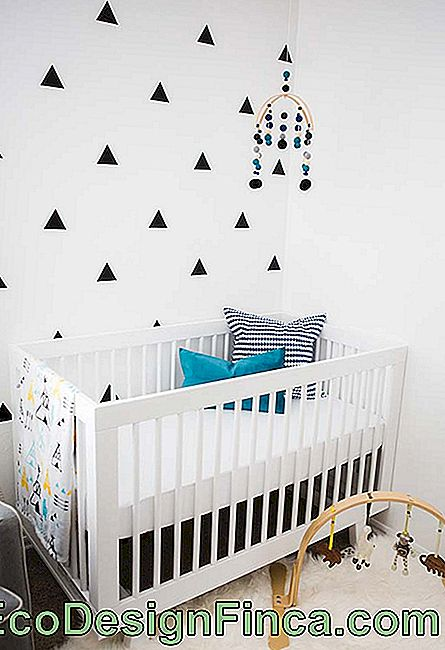 In questa baby room, la carta da parati ricorda un'applique patchwork