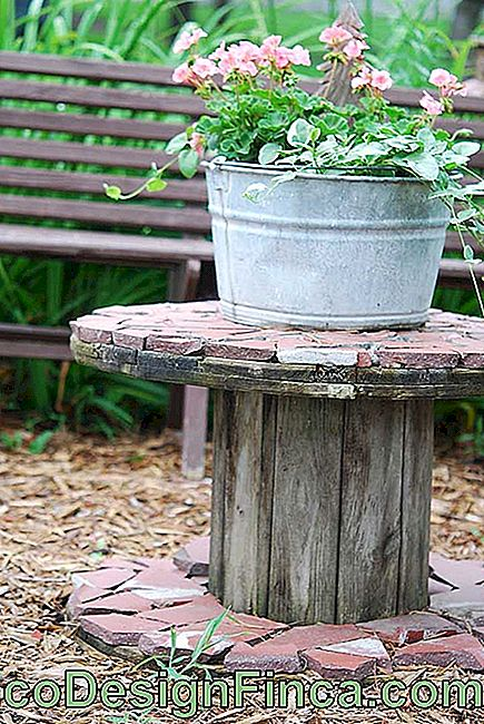 In the garden, the wooden coil was given a rustic mosaic and became perfect to shelter the little plants