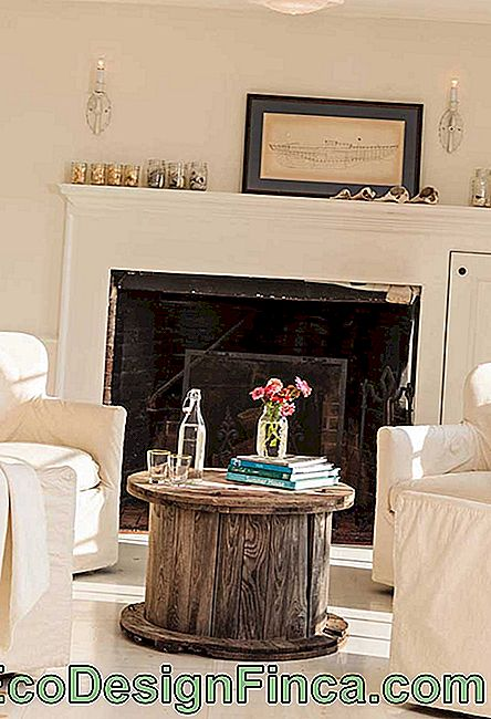 In this clean and well lit room, the rustic spool table forms a lovely double with the fireplace in the back