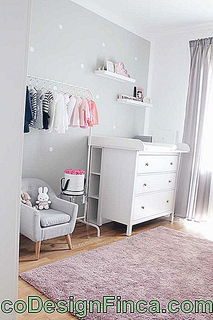 Chest of drawers for white baby room with niches at the back; the open closet completes the look of the environment