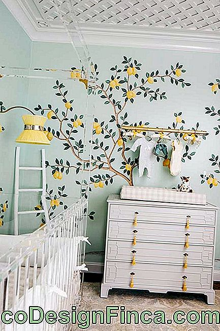 The white dresser in this baby's room has won distinctive handles to match the wallpaper