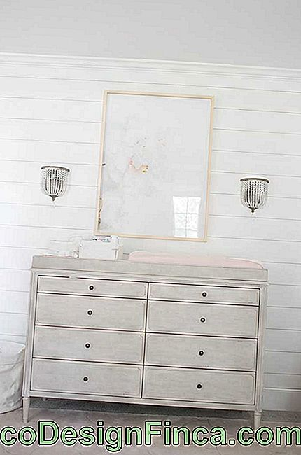 The lightly worn baby dresser brings a rustic and delicate look to the little room