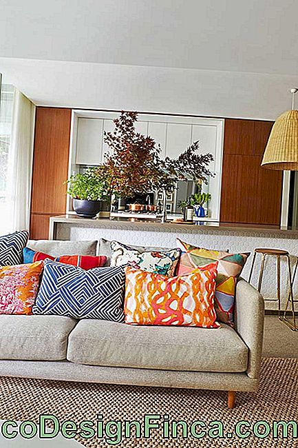 The beige chenille sofa became even more comfortable with the numerous colorful cushions on it